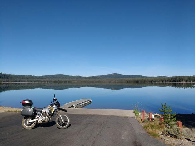 Motorcycle in front of lake with mountains