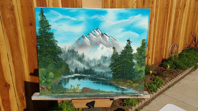Painting of mountain and pond with trees.